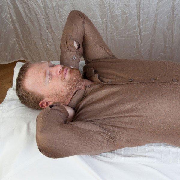 Meditation: Mann am Rücken mit den Händen unter dem Nacken